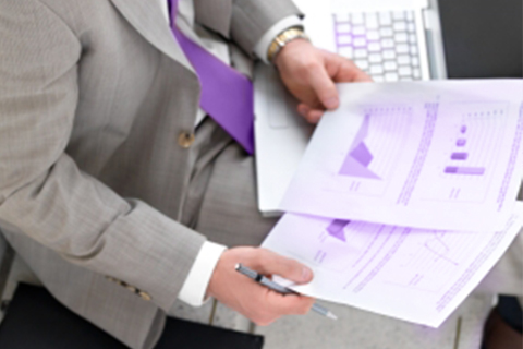 Close up picture of a business man with purple tie, exhaminating some paper with the Analysis result and charts, with a laptop at his side